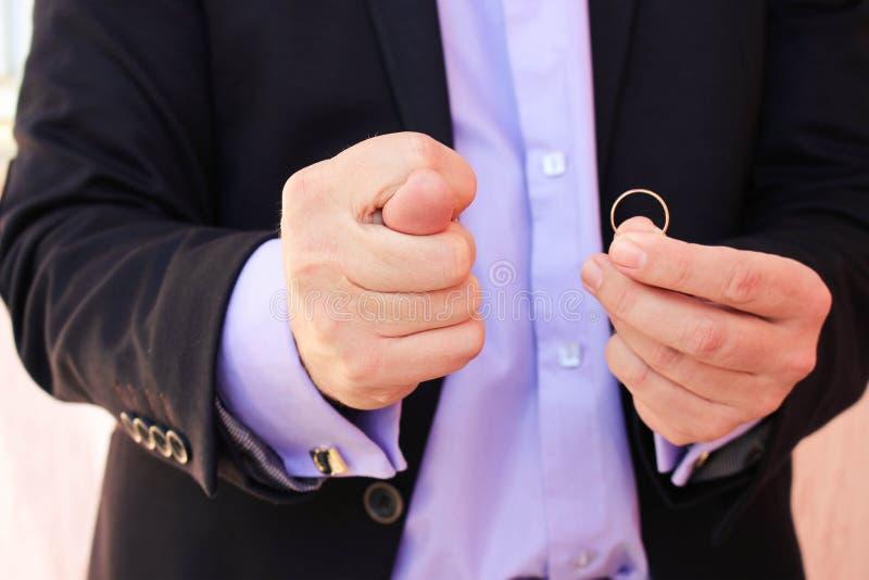 Un hombre en un traje de negocios muestra figo, por otra parte muestra un anillo de bodas El concepto del hombre no quiere casars fotografía de archivo libre de regalías