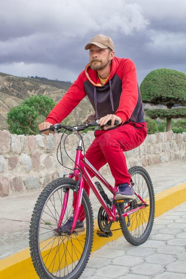 Un hombre en una bicicleta en el aire abierto, paseos a lo largo del camino Acontecimientos deportivos, el montar de los deportes fotos de archivo libres de regalías