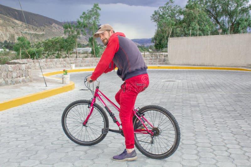 Un hombre en una bicicleta en el aire abierto, paseos a lo largo del camino Acontecimientos deportivos, el montar de los deportes fotografía de archivo libre de regalías