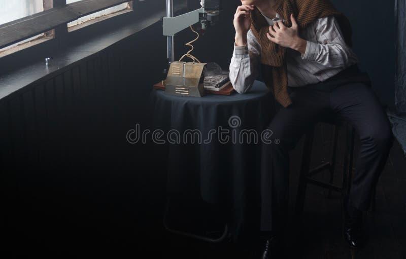 Un hombre en una camisa blanca y un suéter marrón se sienta en un cuarto por la ventana fotografía de archivo