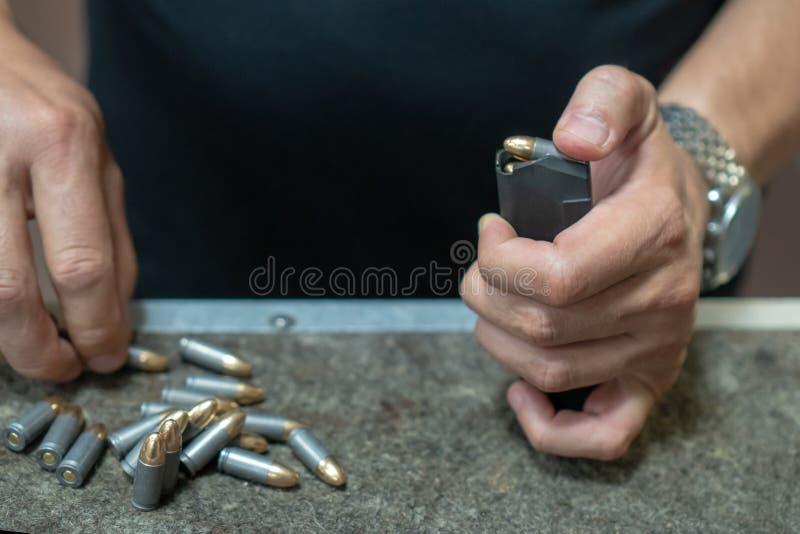 Un hombre en una camiseta negra encarga el tenedor de la pistola de 9 19 cartuchos Las manos de los hombres encargan el arma de l fotos de archivo libres de regalías