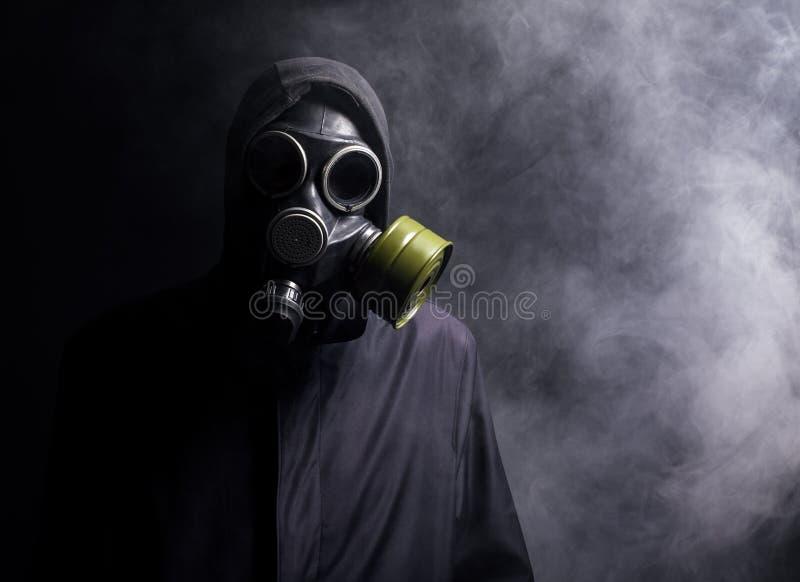 Un hombre en una careta antigás en el humo imagenes de archivo