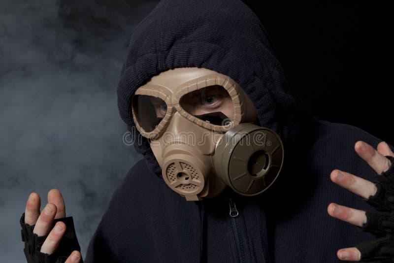 Un hombre en una careta antigás en el humo fotos de archivo libres de regalías