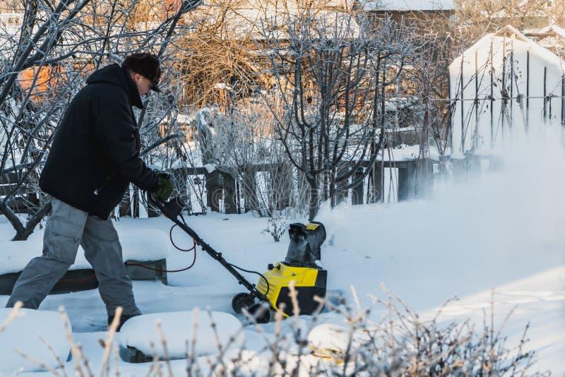 Un hombre en una chaqueta negra y los pantalones grises está cepillando la nieve blanca con el lanzador de nieve eléctrico amaril fotografía de archivo