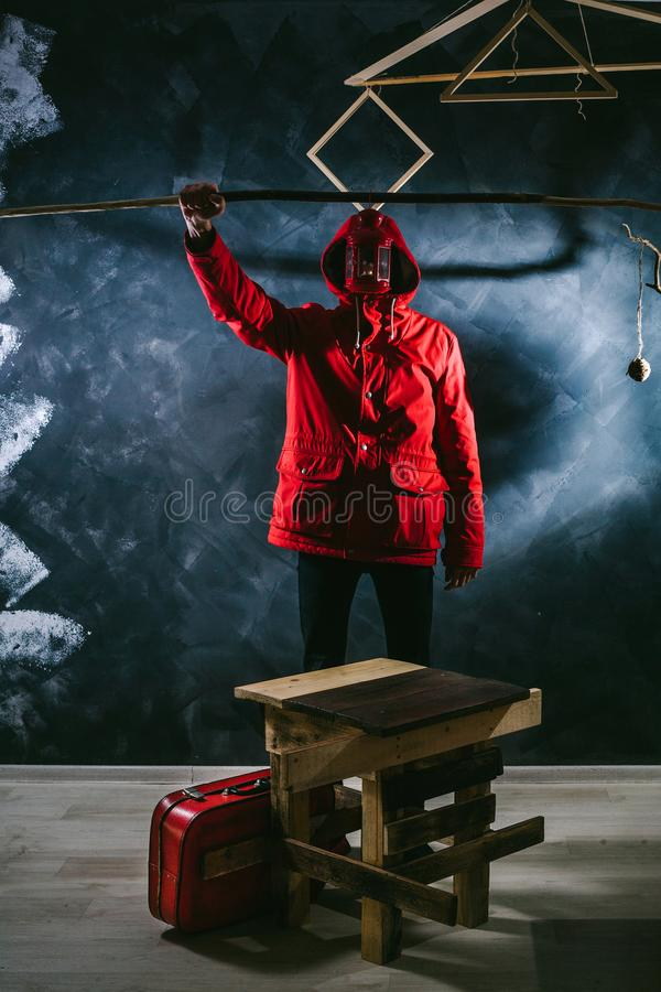 Un hombre en una chaqueta roja contra un fondo negro guarda la palmatoria el cubrir de su cara foto de archivo libre de regalías