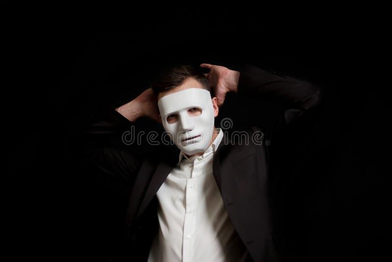 Un hombre en una máscara blanca en un fondo negro abandona Lleva a cabo sus manos detrás de su cabeza imagen de archivo