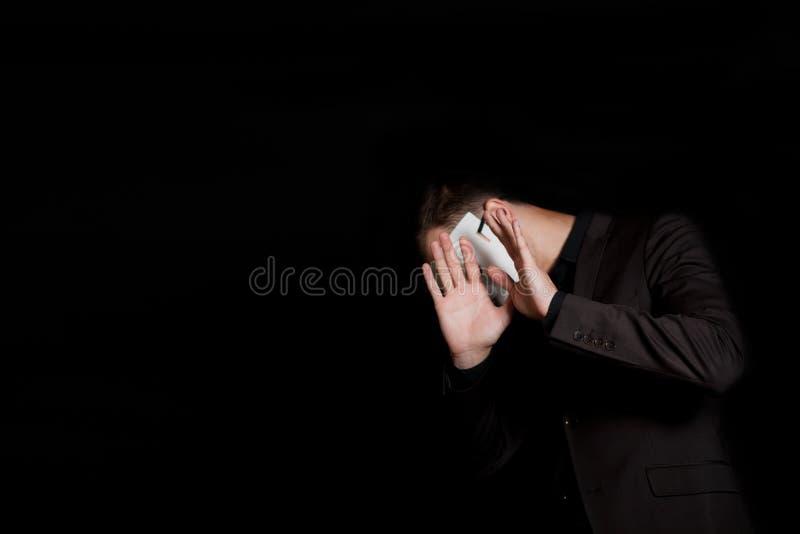 Un hombre en una máscara blanca en un fondo negro Brazos su cara con sus manos c?lera foto de archivo libre de regalías