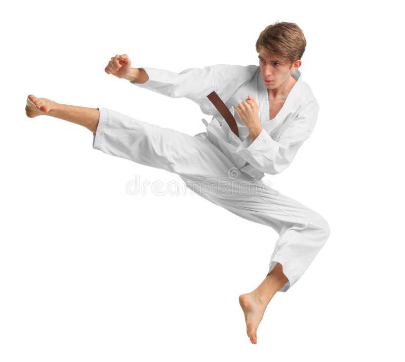 Un hombre en una posición del karate Aislado en el fondo blanco foto de archivo