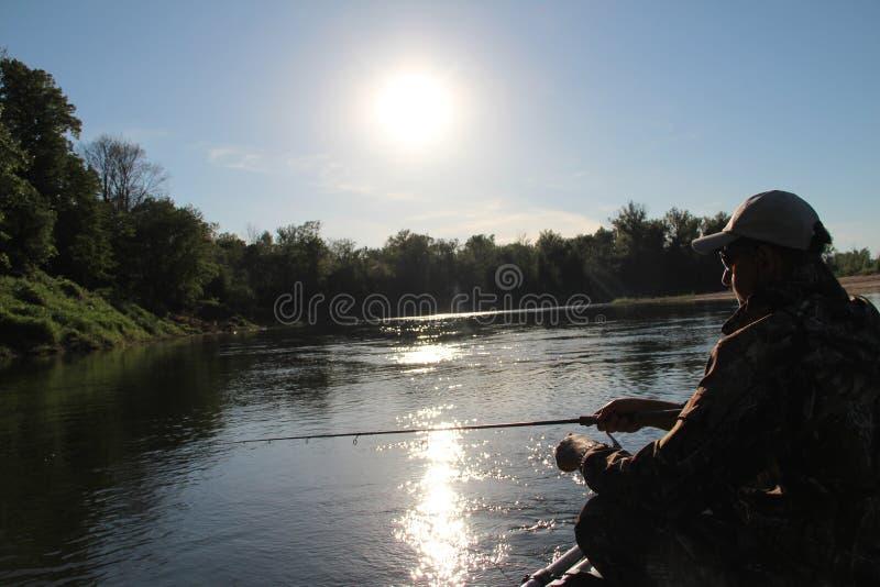 Un hombre en una sentada y una pesca del barco de pesca de la mañana imagen de archivo libre de regalías