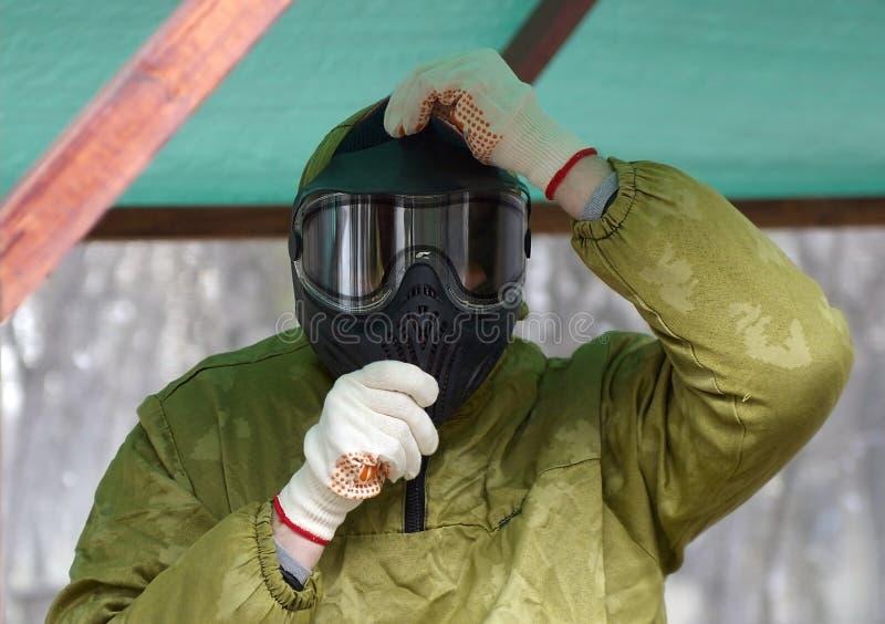 Un hombre en un uniforme especial, llevando un camuflaje para la protección al jugar Paintball imagen de archivo libre de regalías