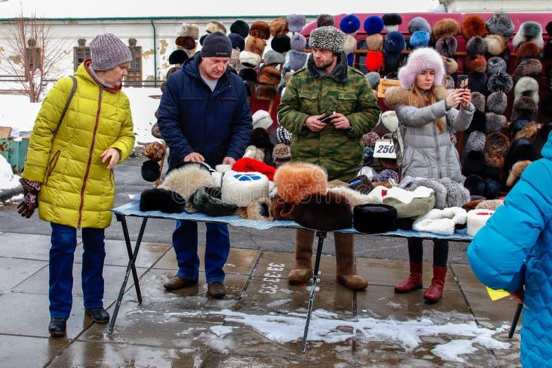 Un hombre en uniforme vende los sombreros del invierno durante una festividad nacional imagen de archivo