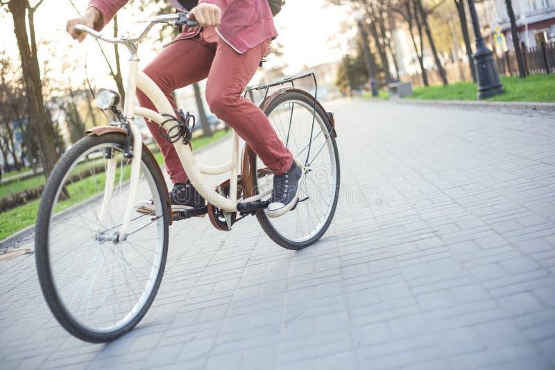 Un hombre en vaqueros rojos y zapatillas de deporte en una bici beige imagenes de archivo