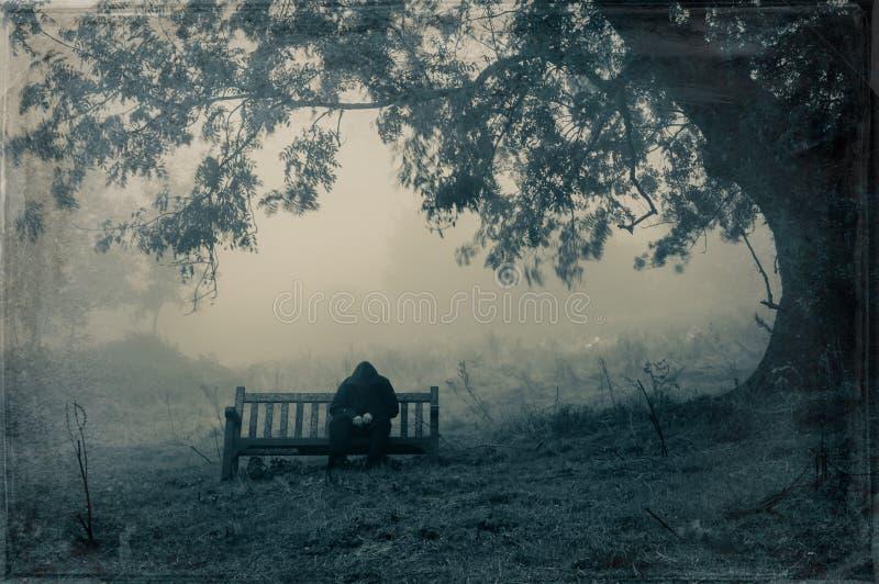 Un hombre encapuchado triste que se sienta en un banco en el campo que mira abajo de la cámara en un día brumoso, cambiante Con u imagen de archivo