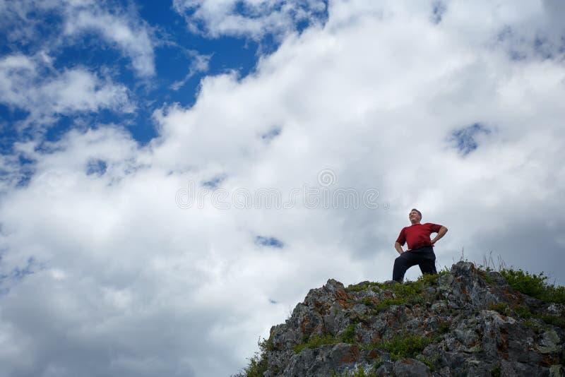 Un hombre encima de una montaña contra un cielo azul con las nubes fotos de archivo