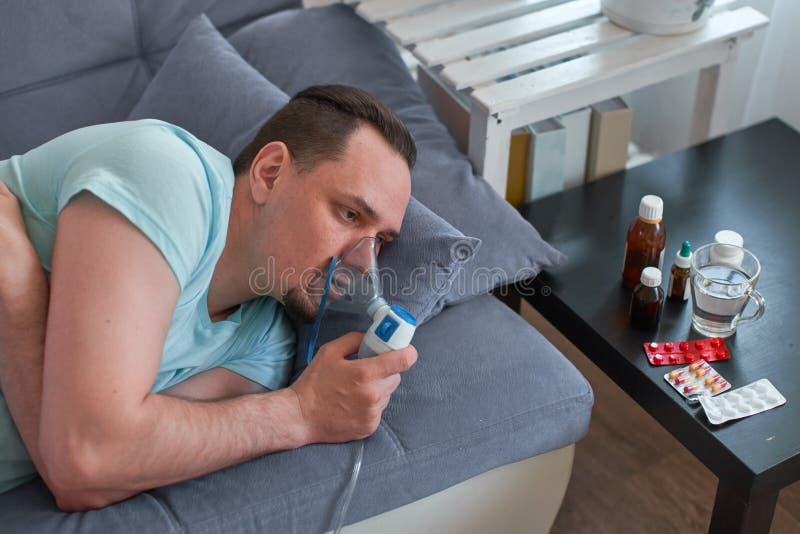 Un hombre enfermo respira a través de una máscara del inhalador mentira en el sofá que lleva a cabo una máscara del nebulizador fotografía de archivo