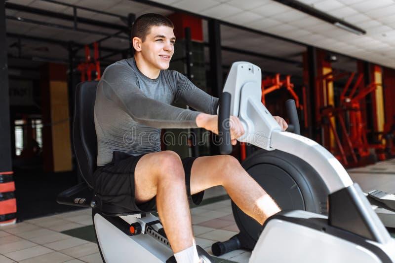 Un hombre enganchó al entrenamiento en una bici de los deportes en el gimnasio, entrenamiento de la mañana fotos de archivo libres de regalías