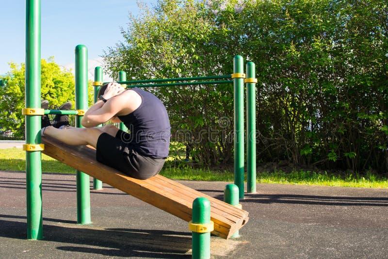 Un hombre entra para los deportes al aire libre, en una plataforma especial, hace un ejercicio en una prensa imágenes de archivo libres de regalías