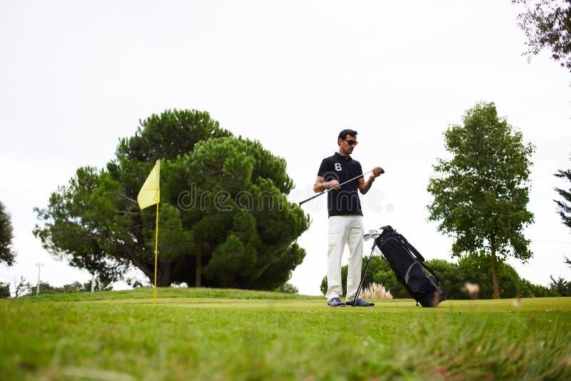 Un hombre es rico y confiado en polo elegante pasa el tiempo que juega a golf El golfista profesional frota un palillo antes de i foto de archivo libre de regalías