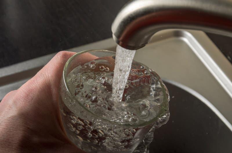 Un hombre escoge el agua para arriba potable en un vidrio de debajo el grifo de la cocina fotografía de archivo libre de regalías