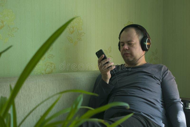 Un hombre escucha la música en el teléfono fotografía de archivo