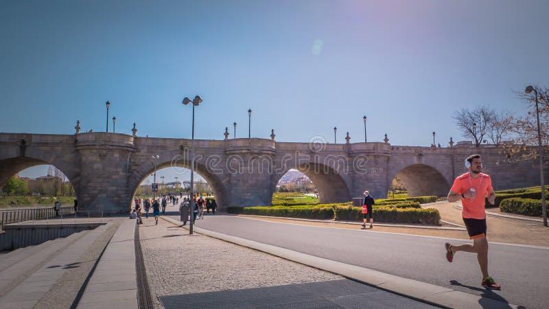 Un hombre está corriendo delante del puente medieval de Toledo en el parque de Madrid Río en España foto de archivo