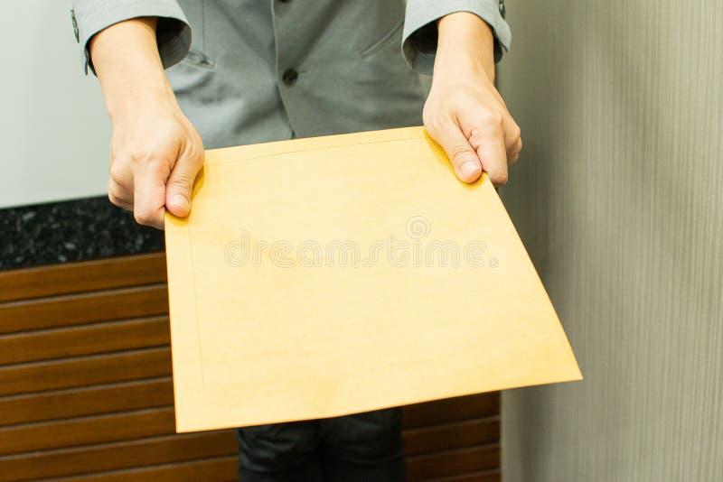 Un hombre está dando un sobre marrón imagen de archivo libre de regalías