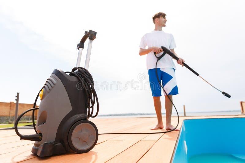 Un hombre está limpiando una piscina fotos de archivo