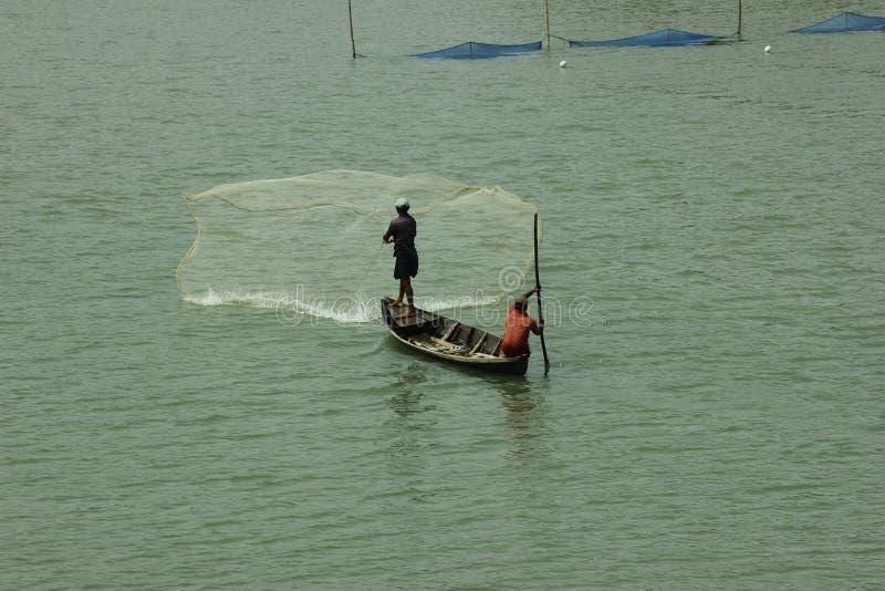 Un hombre está pescando en un barco en el canal de Rizu de la playa de Inani en Bangladesh Cox& x27; Bazar de s fotografía de archivo