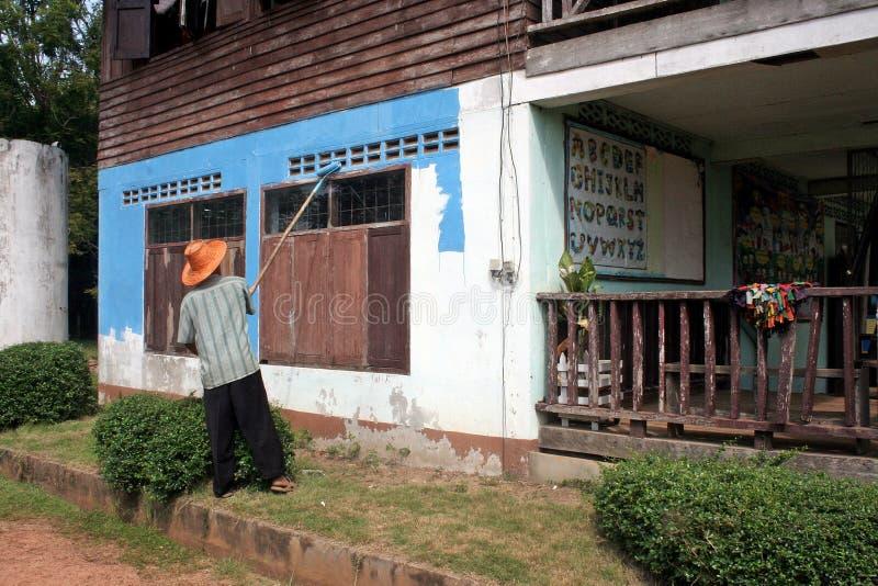 Un hombre está pintando en la pared foto de archivo