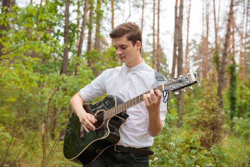Un hombre está tocando una guitarra al aire libre imagenes de archivo
