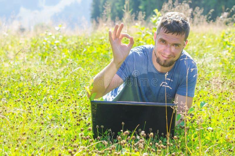 Un hombre está trabajando en un ordenador portátil en naturaleza y muestra una autorización de la muestra, libre imagenes de archivo