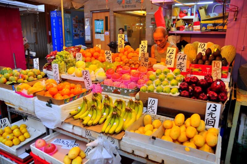 Un hombre está vendiendo en una cabina de la fruta en el og Hong Kong de la calle fotos de archivo libres de regalías
