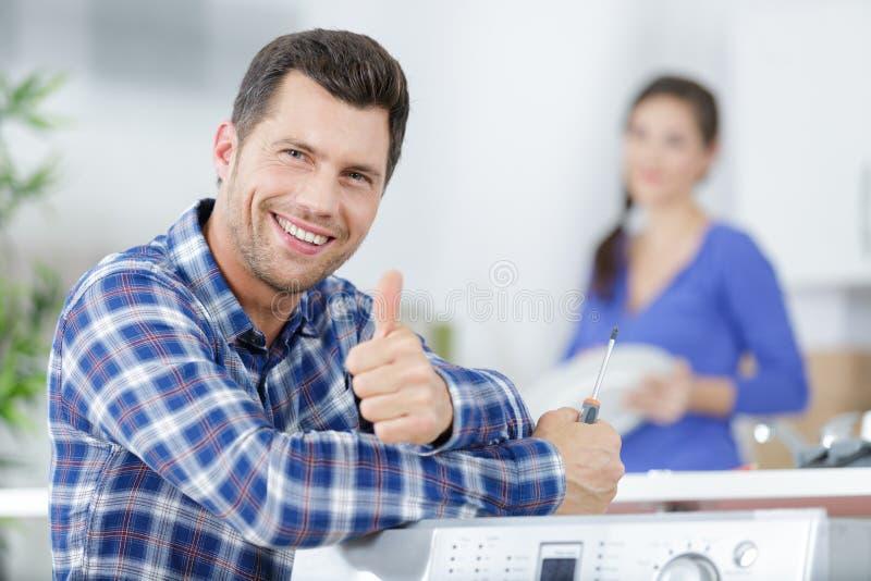 Un hombre feliz y guapo muestra el pulgar en la cocina fotografía de archivo