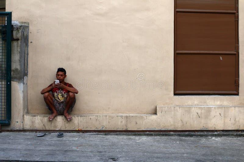 Un hombre filipino adulto descansa fuera de un edificio y juega a un juego en su smartphone fotos de archivo libres de regalías