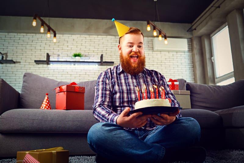 Un hombre gordo con una torta de cumpleaños en el cuarto fotos de archivo libres de regalías