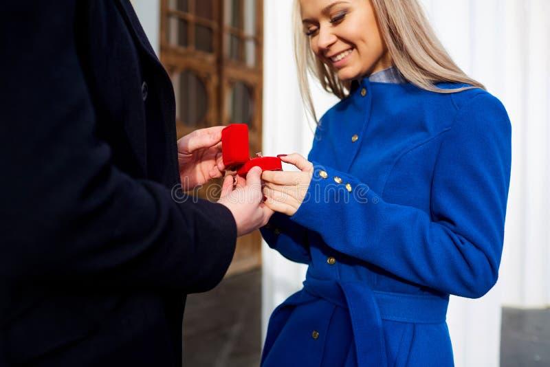 Un hombre hace una propuesta de matrimonio a su novia al aire libre fotografía de archivo