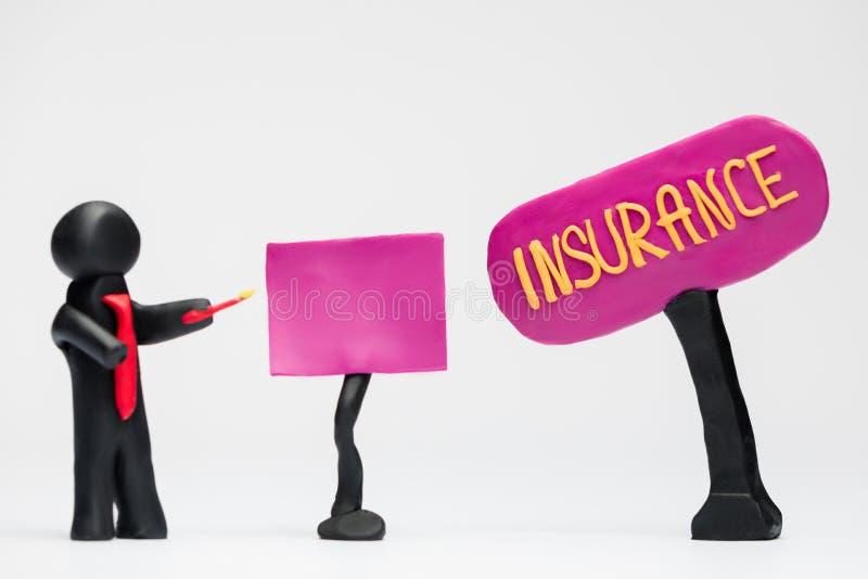 Un hombre hecho del plasticine que hace una presentación sobre seguro, en el fondo blanco foto de archivo libre de regalías