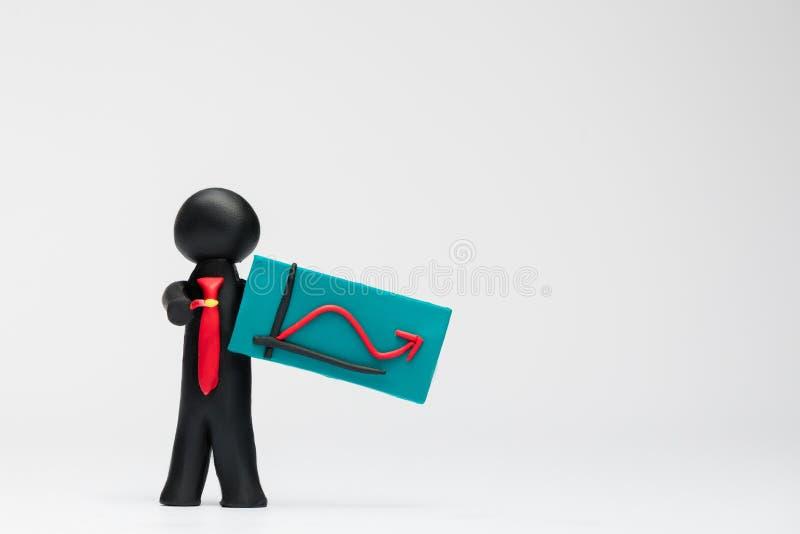 Un hombre hecho del plasticine que lleva a cabo un gráfico con una flecha que señala para arriba en el fondo blanco, alineado a l fotografía de archivo