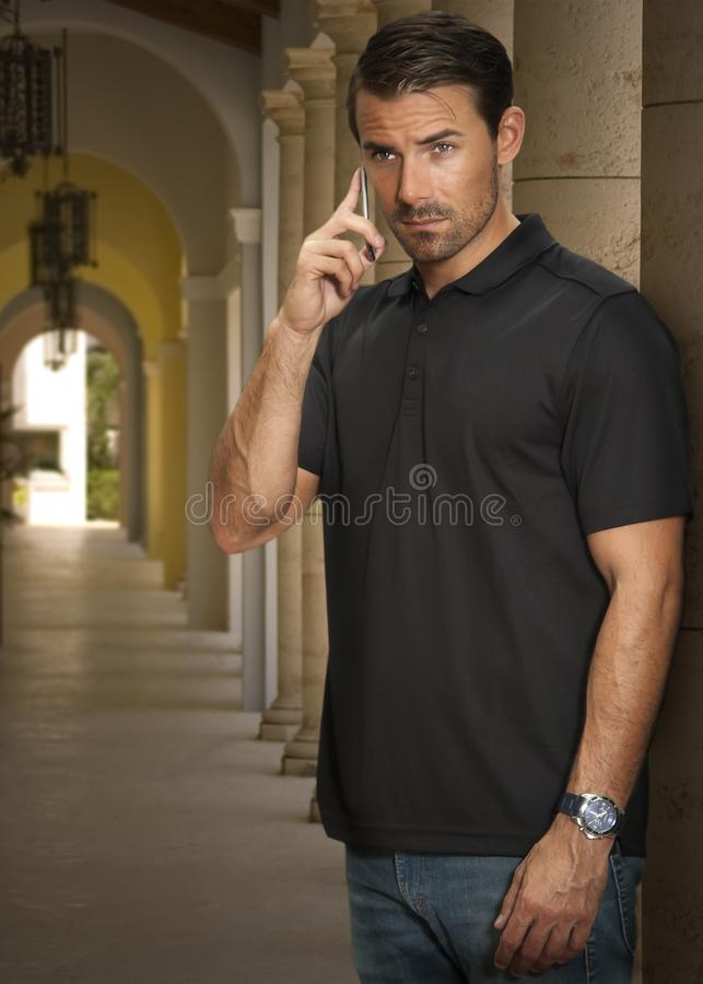 Un hombre hermoso escucha un teléfono celular imágenes de archivo libres de regalías