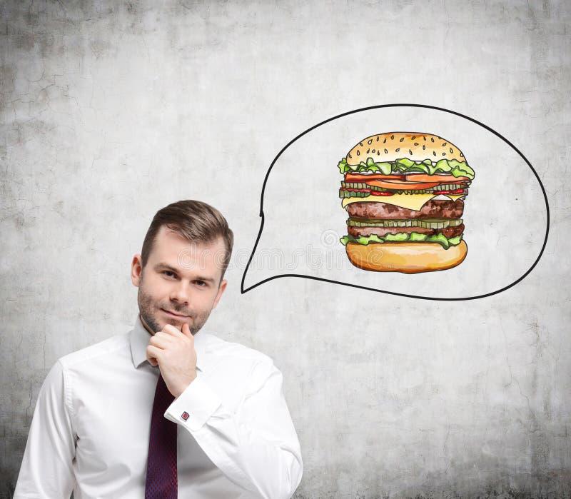Un hombre hermoso está pensando en la hamburguesa Un concepto de los alimentos de preparación rápida fotos de archivo libres de regalías