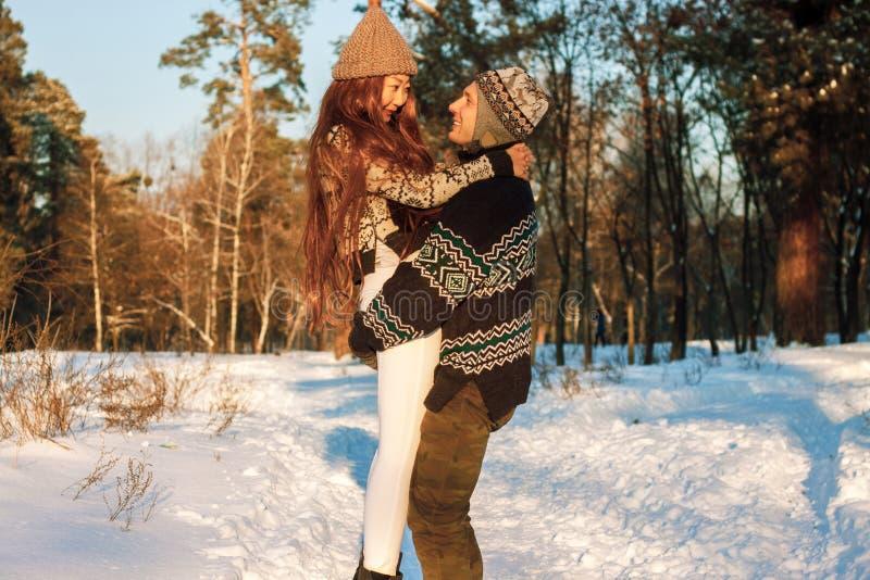 Un hombre hermoso joven de aspecto europeo y una muchacha asiática joven en un parque en la naturaleza en invierno foto de archivo libre de regalías