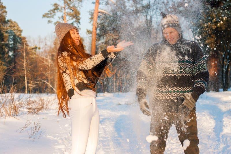 Un hombre hermoso joven de aspecto europeo y una muchacha asiática joven en un parque en la naturaleza en invierno imagen de archivo