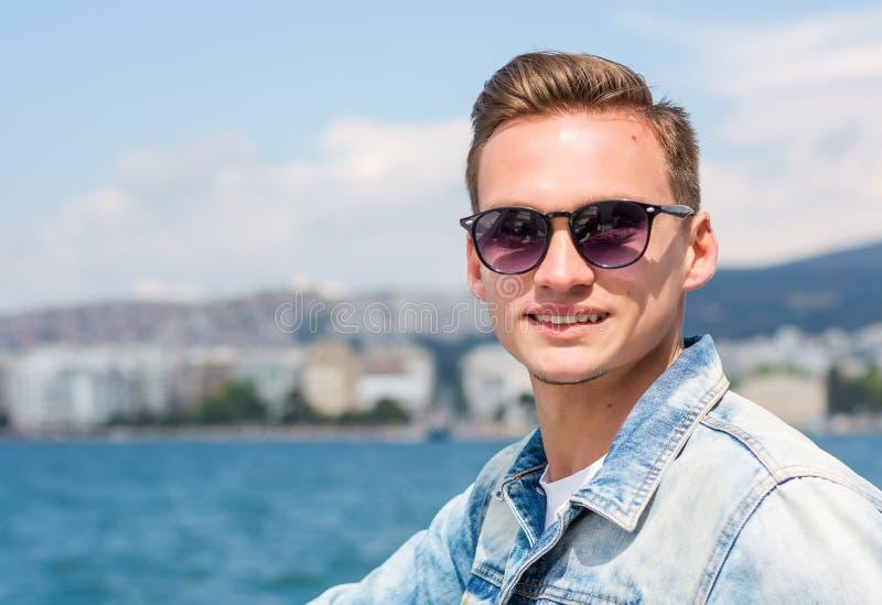 Un hombre hermoso joven en el fondo del paisaje marino en primavera imagen de archivo libre de regalías