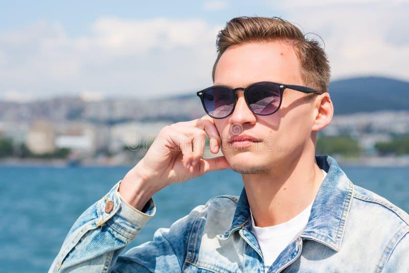 Un hombre hermoso joven en gafas de sol en el fondo del paisaje marino imágenes de archivo libres de regalías