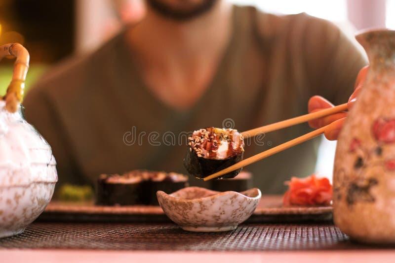 Un hombre hermoso joven está comiendo los rollos de sushi con los palillos en un restaurante japonés y un té de consumición imagenes de archivo