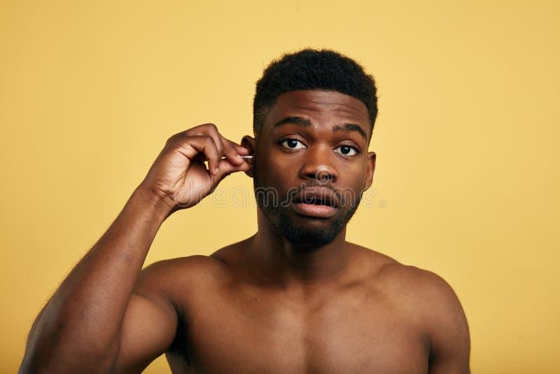 Un hombre hermoso joven limpia los oídos sucios con una esponja de algodón blanca imagenes de archivo