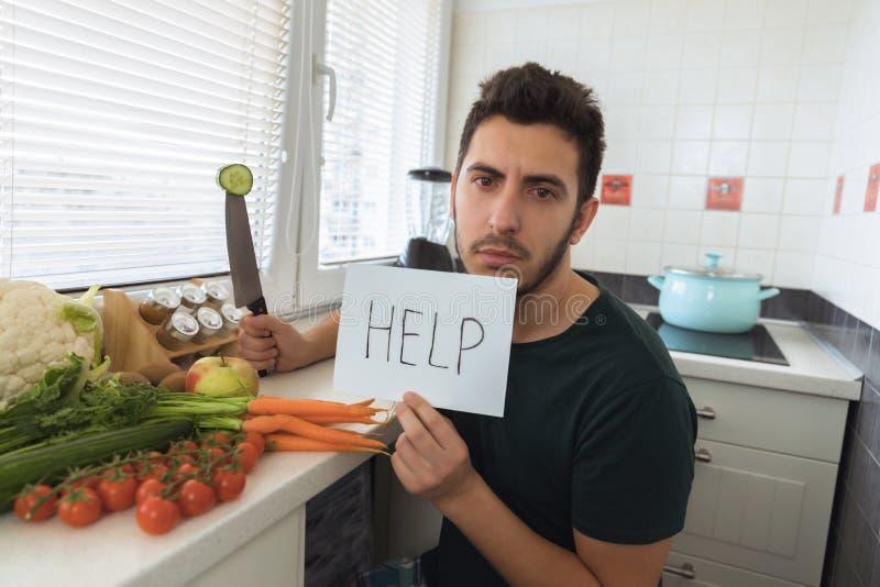Un hombre hermoso joven se sienta en la cocina con una cara enojada y pide ayuda foto de archivo libre de regalías