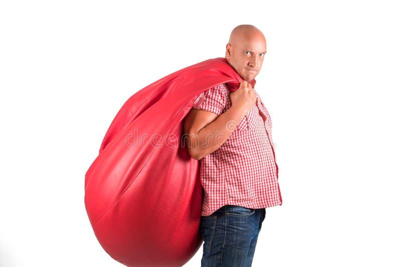 Un hombre hermoso, positivo en un fondo blanco en la camisa guarda la silla del bolso fotos de archivo libres de regalías