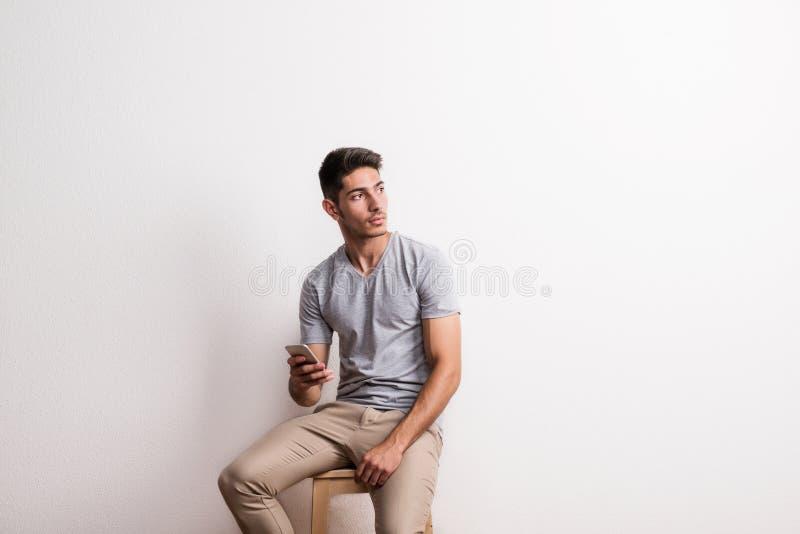Un hombre hispánico joven alegre con el smartphone que se sienta en un taburete en un estudio imágenes de archivo libres de regalías