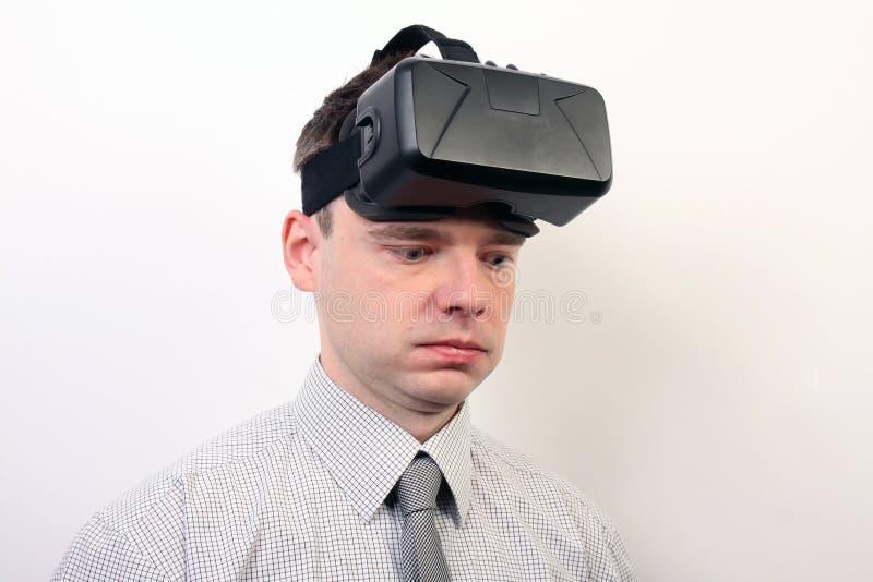 Un hombre impresionado, mareado, pasmado que lleva las auriculares de la realidad virtual de la grieta VR de Oculus fotografía de archivo